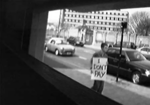 """person holding a sign that says """"I don't pay"""" past a shop window as seen through a cheap camera."""