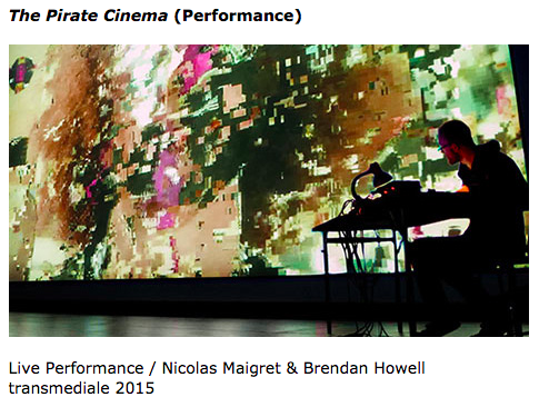 """pixels cut together on a screen projection behind someone sat at a desk. """"The Pirate Cinema (Performance) Live Performance / Nicolas Maigret & Brendan Howell transmediale 2015"""""""