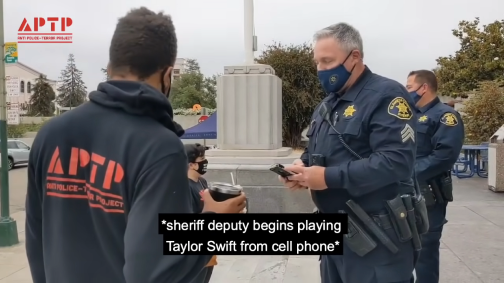 """screen grab of video stream showing two people, one dressed as a police officer holding a phone, the subtitles say: """"*sheriff deputy begins playing Taylor Swift from cell phone*"""""""