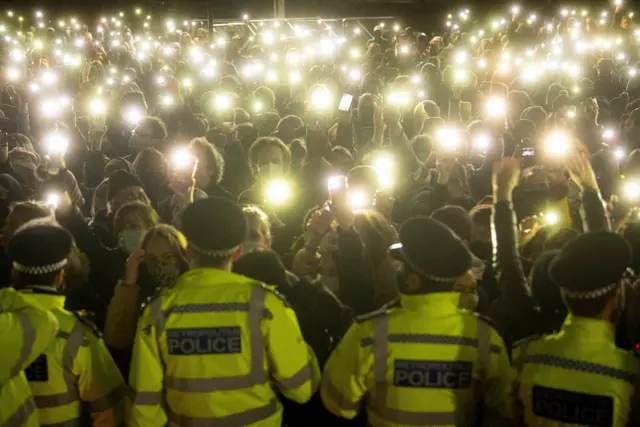 Sarah Everard vigil in Clapham Common. women shine their camera lights at police blocking the vigil.